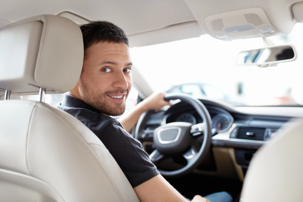 Young male at the wheel enjoying Maximum Collision Valet Service