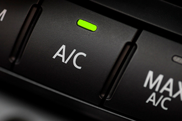 Air conditioning repair with a close up of the A/C button