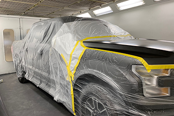 Car all taped up in a paint booth ready for painting