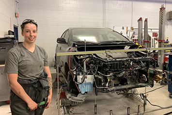 Small image of a Female employee working on a damaged car's front end
