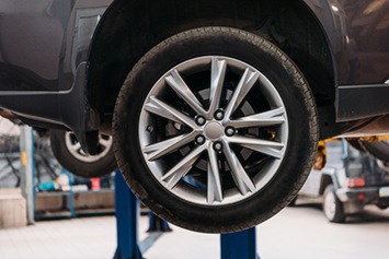 Small image of Wheel alignment showing the tire of a car up on a hoist